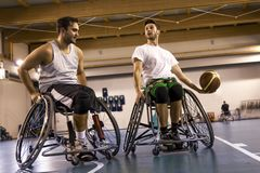 Disabled sport men in action while playing basketball. Disabled sport men in action while playing indoor basketball at a basketball court royalty free stock image