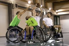 Disabled sport men in action while playing basketball. Disabled sport men in action while playing indoor basketball at a basketball court stock photo