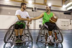 Disabled sport men in action while playing indoor basketball. At a basketball court Royalty Free Stock Image