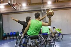 Disabled sport men in action while playing indoor basketball. At a basketball court royalty free stock photography