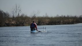 Rear view of Disabled sportsman rowing on the river in a canoe. Rowing, canoeing, paddling. Training. Kayaking. Disabled sportsman rowing on the river in a canoe stock video