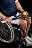Disabled sportsman sitting in wheelchair and holding tennis racquet with ball Stock Photography
