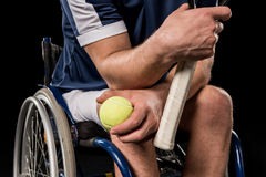 Disabled sportsman sitting in wheelchair and holding tennis racquet with ball Stock Image