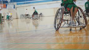 Disabled sportsmen plays wheelchair basketball. Wide angle Royalty Free Stock Image