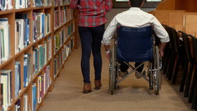Disabled student and friend in the library stock video footage