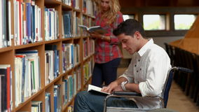Disabled student reading in the library stock video footage