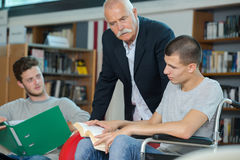 Disabled student in school library with friend and librarian. Disabled student in the school library with friend and librarian Royalty Free Stock Photography