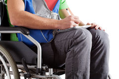 Disabled student writing the notes. Student on wheelchair writing the notes on his knees Royalty Free Stock Image