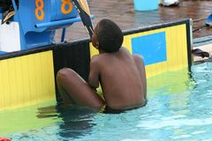 Disabled swimmer. Holding towel with teeth start Royalty Free Stock Photography