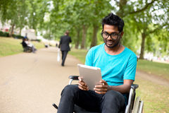 Disabled technology. Disabled man in the park with a tablet computer Royalty Free Stock Photo
