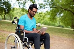 Disabled technology. Young indian man in a wheelchair using a tablet computer Stock Photos