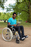 Disabled technology. Young man in a wheelchair using a tablet computer Royalty Free Stock Image