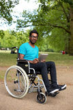 Disabled technology. Young man in a wheelchair using a tablet computer Royalty Free Stock Images