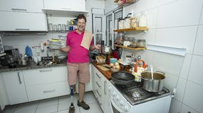 disabled uomo senza gamba Pulitura della cucina immagine stock