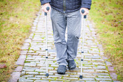 Disabled veteran on crutches at cemetery Royalty Free Stock Photography