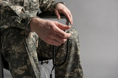 Disabled veteran holding rosary in hand. Close up of male hand holding beads. Man is sitting in wheelchair and wearing military uniform.  on grey background Royalty Free Stock Photos