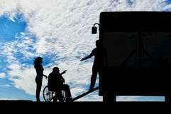 Disabled in wheelchair nurse helping to climb ramp in bus. Disabled person in wheelchair to help climb the ramp in bus day. Concept help disabilities Royalty Free Stock Photo