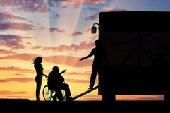 Disabled in wheelchair nurse helping to climb ramp in bus sunset. Disabled person in wheelchair to help climb the ramp in bus sunset. Concept help disabilities Stock Photo