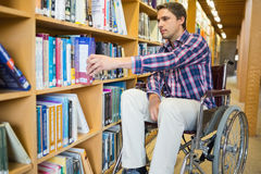 Disabled wheelchair selecting book in library Royalty Free Stock Photo