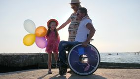Happy family, disabled in wheelchair stroll with pregnant wife, child holds air balloons and jumping, invalid with wife