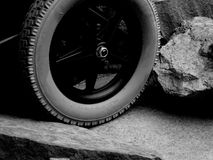 A Single Wheel of a Disabled Wheelchair Between Rocks and Stone stock photo