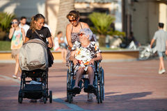 Disabled with wheelchair. Woman with pram. Women generation. A woman pushes a wheelchair with a child inside. A woman pushing the wheelchair with his mother over Royalty Free Stock Images