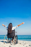 Disabled woman with arms outstretched at the beach. On a sunny day stock photography