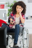 Disabled woman bored watching tv in living room Royalty Free Stock Image