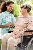 Disabled woman and caring doctor. Disabled women and caring doctor in the garden Royalty Free Stock Image
