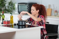 Disabled woman cooking in kitchen. Disabled woman cooking in her kitchen Royalty Free Stock Photography