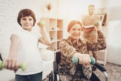 Disabled Woman Dumpbells Exercises With A Son. Disabled Woman In A Wheelchair. Dumpbells Exercises With A Son. Meeting After War. Camouflage Uniform. Paralyzed royalty free stock image