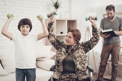 Disabled Woman Dumpbells Exercises With A Son. Disabled Woman In A Wheelchair. Dumpbells Exercises With A Son. Meeting After War. Camouflage Uniform. Paralyzed stock photos