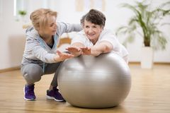 Disabled woman exercising on the ball with physiotherapist royalty free stock photo