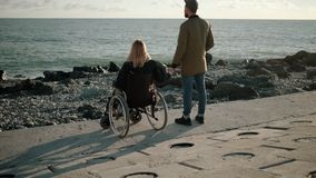 Woman is sitting in wheelchair on sea coast and holding hand of her husband stock video
