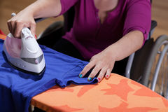 Disabled woman during ironing Stock Photography