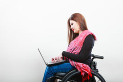 Disabled woman with laptop on wheelchair. Stock Image
