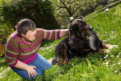 Disabled woman on a lawn with dog. Disabled woman on a lawn is stroking a dog Royalty Free Stock Photos