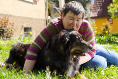 Disabled woman is lying on a lawn. Mentally disabled woman is lying with dog on a lawn Royalty Free Stock Photography