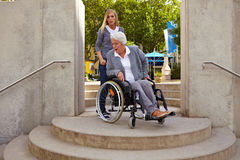 Disabled woman is mad at staircase. Elderly woman in wheelchair looking at inaccessible staircase Royalty Free Stock Photography