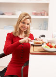Disabled Woman Making Sandwich In Kitchen Stock Photo