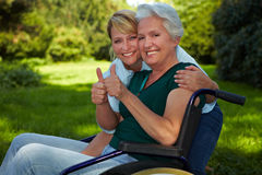 Disabled woman and nurse holding royalty free stock photos