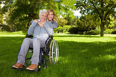 Disabled woman in a park. Happy woman in wheelchair with young woman in nature Stock Image