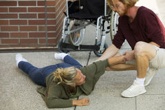 Disabled woman on pavement next to wheelchair getting help Royalty Free Stock Images