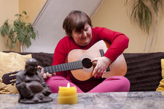 Disabled woman plays guitar and is happy Stock Image