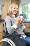 Disabled Woman Sitting In Wheelchair At Home With Hot Drink Stock Image