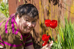 Disabled woman smells on a flower Stock Photos