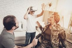 Disabled Woman Soldier Family Are Having Fun. Meeting After War. Son And Husband. Camouflage Uniform. Virtual Reality Glasses. Paralyzed Soldier. Homecoming royalty free stock images