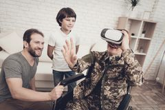 Disabled Woman Soldier Family Are Having Fun. Meeting After War. Son And Husband. Camouflage Uniform. Virtual Reality Glasses. Paralyzed Soldier. Homecoming stock photos