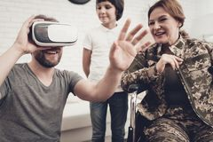 Disabled Woman Soldier Family Are Having Fun. Meeting After War. Son And Husband. Camouflage Uniform. Virtual Reality Glasses. Paralyzed Soldier. Homecoming stock photo