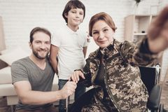 Disabled Woman Soldier Makes A Family Selfie. Disabled Woman In A Wheelchair Makes A Selfie With Family. Meeting After War. Son And Husband. Camouflage Uniform stock images